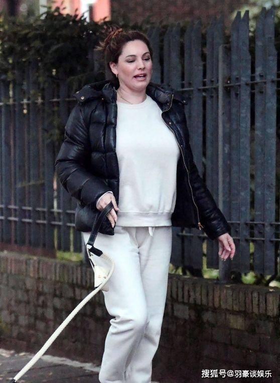 亚博APP手机版:凯利布鲁克穿着白色西装和黑色羽绒服遛狗非常舒服
