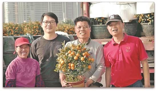 农田里长出幸福年花梁满坤(右一)和花农们为众多群众送春节祝