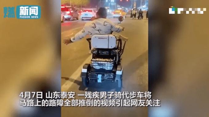 残疾人坐代步车沿路推倒路障 !目击者:环卫工跟在后面扶正